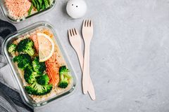 Meal prep lunch box containers with baked salmon fish, rice, green broccoli stock images