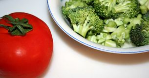 Meal Preparation. Tomato with stem next to a bowl of cut up broccoli Stock Images