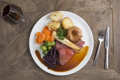 Traditional roast beef dinner with wine. A meal of rare roast beef with carrots, sprouts, red cabbage, parsnips, Yorkshire pudding and red cabbage on a wooden stock photos