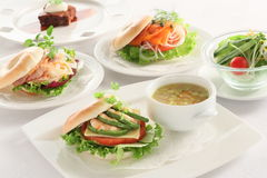 Meal table of hamburger with shrimp, salmon, chicken, vegetables Royalty Free Stock Photos