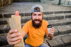 Meal that tastes right. Bearded man eating unhealthy food during rest and meal break. Hipster eating hot dog meal on stock images