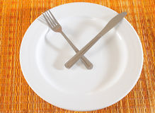 Meal time. Fork and knife in time setting over an empty plate Stock Photography