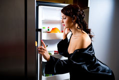 Meal Time. Young woman looking for something to eat inside the fridge stock image