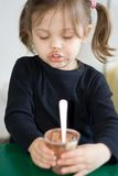 Meal time. Little girl eating her chocolate pudding Stock Images