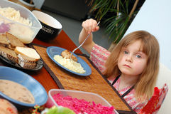 Meal time. Little girl siiting at the table full of food with a fork in her hand Stock Images