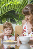 Meal time. Portrait of young woman feeding her baby daughter Royalty Free Stock Images
