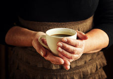 Hands of senior woman holding cup of coffee Royalty Free Stock Images
