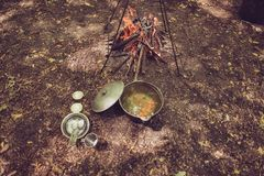 Meal time. High angle view of a soup in a kettle, near the camp stock image