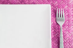 Meal time. Insert food. Table setting with empty square plate, fork and pink mat Royalty Free Stock Images