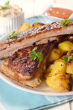 Meal time. Plate with baked potato and beef ribs in bbq sauce,selective focus Stock Photography