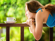 Young woman drinking cofee in a garden Stock Images