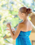 Young woman drinking coffee on morning terrace Stock Image