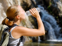 Young woman drinks water by waterfall Royalty Free Stock Photos