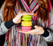 Young woman holding the french pastry macaron in c Royalty Free Stock Photography