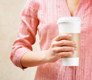Young woman holding a tumbler of coffee.  Stock Images