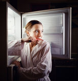 Young woman looking for some snack in fridge late  Royalty Free Stock Photos