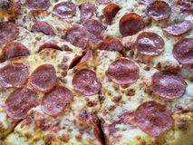 approaching an Italian pizza with pepperoni, background and texture stock photography