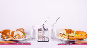 Meal for two. Delicius sandwich with set for dining and cups of tea Stock Images