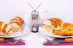 Meal for two with cups. Two delicius sandwiches with cups and set for dining Stock Photography