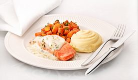Dinner with vegetables, salmon and potatoes on a plate Royalty Free Stock Image