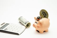 Mealheiro cerâmico com bitcoin dourado na parte superior, nos dólares e na calculadora foto de stock