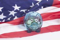 Mealheiro com as moedas na bandeira nacional americana Fotografia de Stock Royalty Free