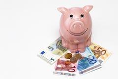 Mealheiro cor-de-rosa com economias no fundo branco Fotografia de Stock Royalty Free