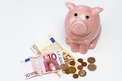 Mealheiro cor-de-rosa com economias no fundo branco Fotografia de Stock