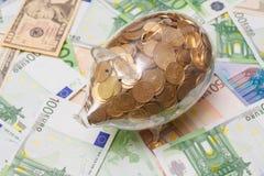 Mealheiro de vidro completamente de moedas douradas sobre um fundo feito contas das cédulas do Euro e do dólar. Imagens de Stock
