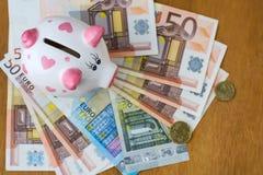 Mealheiro e euro- cédulas em uma tabela de madeira finanças saving imagem de stock