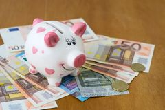 Mealheiro e euro- cédulas em uma tabela de madeira finanças saving fotografia de stock