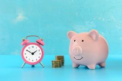 Mealheiro em um fundo de turquesa, ao lado de um despertador cor-de-rosa pequeno e de duas pilhas de moedas fotos de stock royalty free