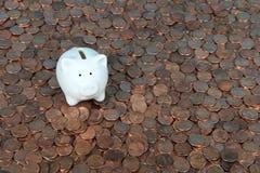 Mealheiro minúsculo na tabela das moedas de um centavo Fotografia de Stock