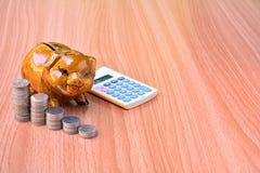 Mealheiro, moedas e calculadora para fora na tabela de madeira Imagens de Stock Royalty Free