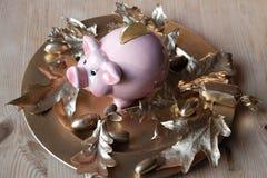 Mealheiro na placa dourada com bolotas e as folhas douradas imagens de stock royalty free