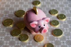 Mealheiro no fundo dourado com moedas do chocolate imagem de stock
