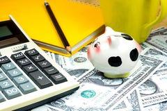 Mealheiro pequeno e calculadora financeira em pilhas do dólar americano Fotos de Stock