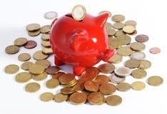 Mealheiro vermelho cercado por moedas Imagens de Stock