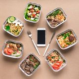 Daily meals delivery. Daily meals in foil boxes and smartphone, top view, flat lay. Healthy food delivery concept. Fitness nutrition for diet stock photo