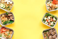 Daily meals delivery. Daily meals in foil boxes on yellow background, top view, copy space. Healthy food delivery concept. Fitness nutrition for diet royalty free stock images