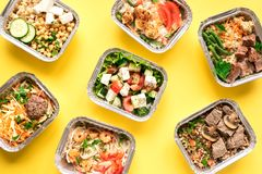 Daily meals delivery. Daily meals in foil boxes on yellow background, top view, flat lay. Healthy food delivery concept. Fitness nutrition for diet royalty free stock photos
