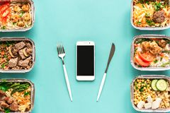 Daily meals delivery. Daily meals in foil boxes and smartphone on blue background, top view, copy space. Healthy food delivery concept. Fitness diet nutrition stock image