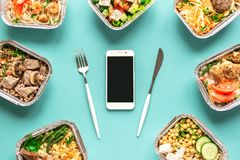 Daily meals delivery. Daily meals in foil boxes and smartphone, top view, flat lay. Healthy food delivery concept. Fitness nutrition for diet royalty free stock images