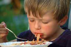 Mealtime in red. Young boy eating spaghetti royalty free stock photos