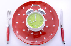 Mealtime table place setting with alarm clock Royalty Free Stock Images