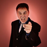 Mean Angry Boss Pointing Finger. A mean angry boss is pointing his finger on an isolated background for a business failure concept Stock Photos