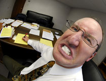Mean Boss in Office. Mean looking man in business office gritting teeth Stock Photos