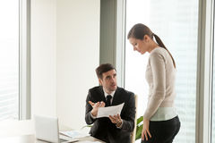 Mean furious boss reprimands incompetent female employee for bad Royalty Free Stock Photography