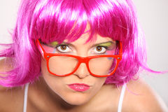 Mean girl. A picture of a young serious woman in purple hair and colorful make-up over light background royalty free stock photo