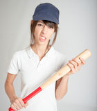Mean girl with bat. Young woman with a baseball bat and a mean expression Stock Photo